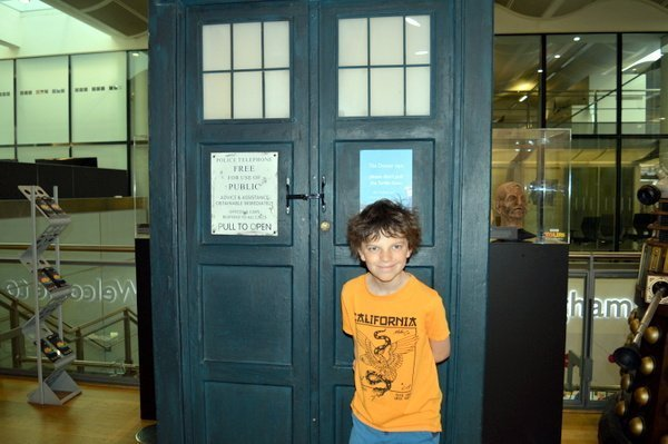 A child standing in front of the Tardis from Dr Who in the BBC Visitor Centre in Brimingham