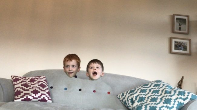 The heads of two boys appears to float on a sofa as they hide under a Harry Potter invisibility cloak
