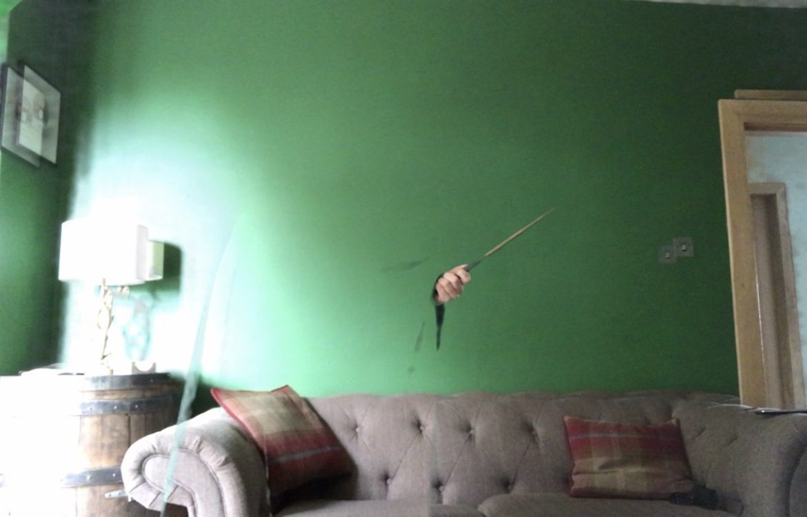 A green room with a sofa, and a hand poking out of an invisibility cloak holding a magic wand