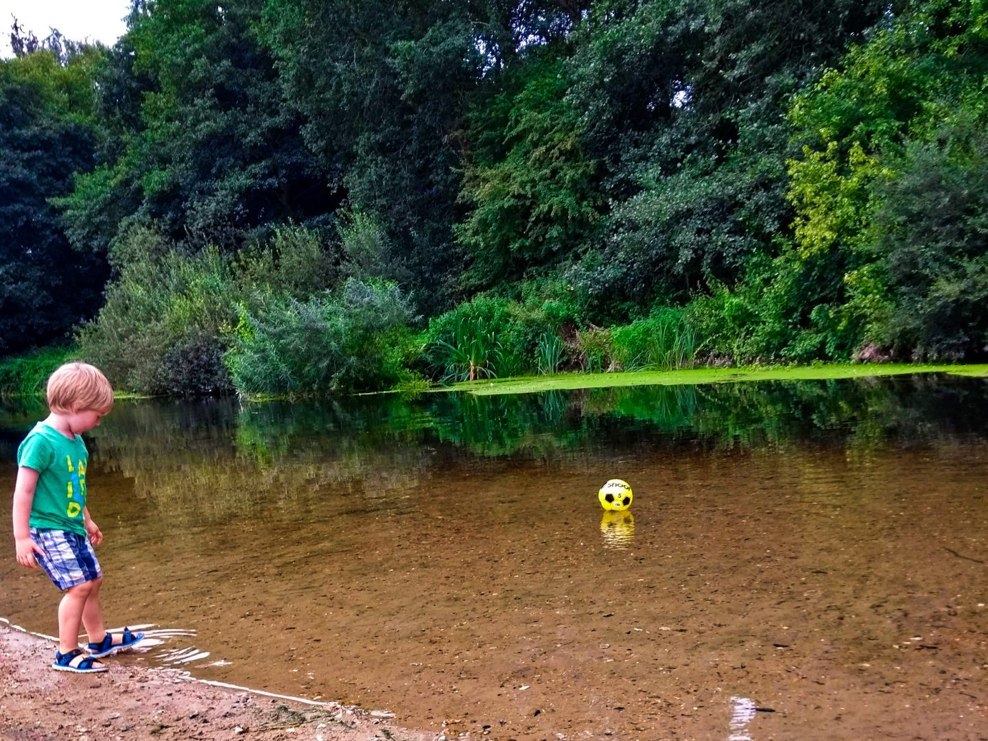A boy next to a river in Santon Downham in Suffolk, with a yellow ball floating on the water and greenery surrounding it