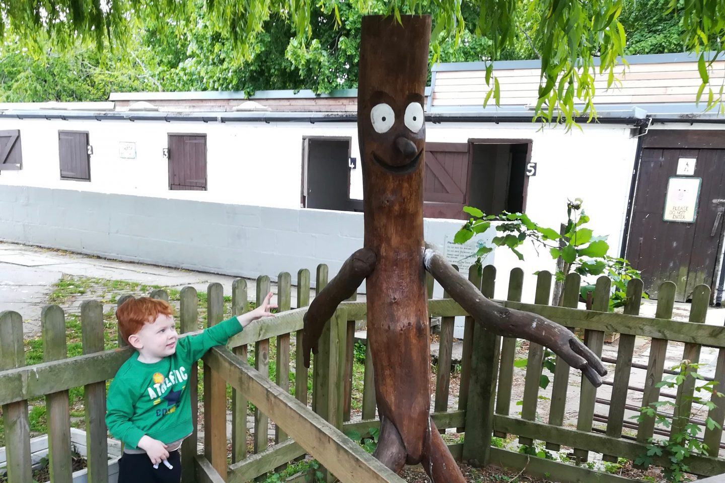 a young child standing next to a large model of Stick Man