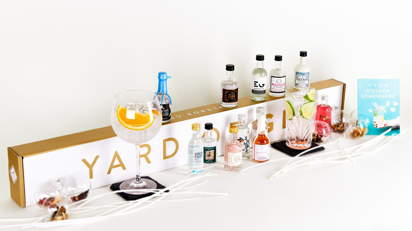 A rectangular box with yard of gin written on it in gold text, surrounded by miniature gin bottles and glasses of gin and tonic