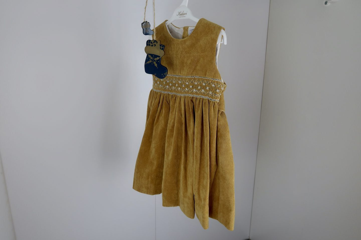 A mustard coloured velvet dress for a young girl hanging up with a white background