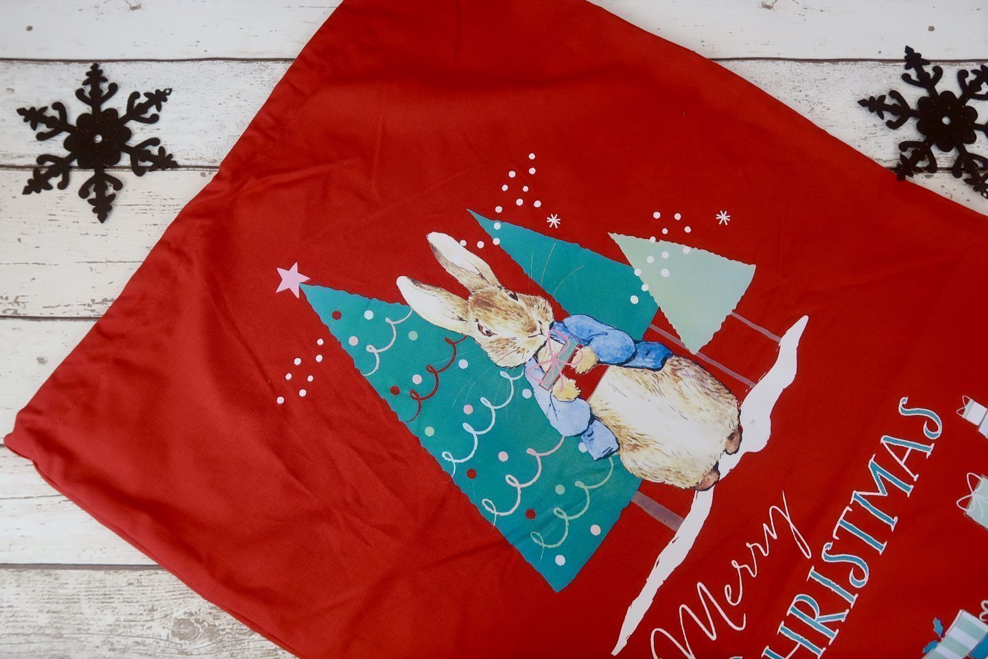 A red sack with Peter Rabbit on it and 3 chirstmas trees