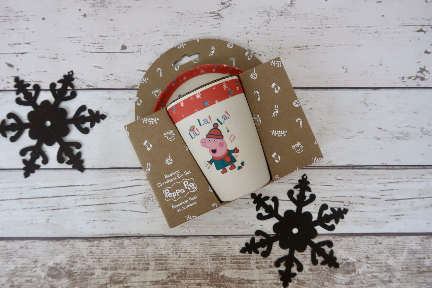 A Peppa Pig Christmas Eve plate and cup in its packaging with 2 metal snowflakes around it