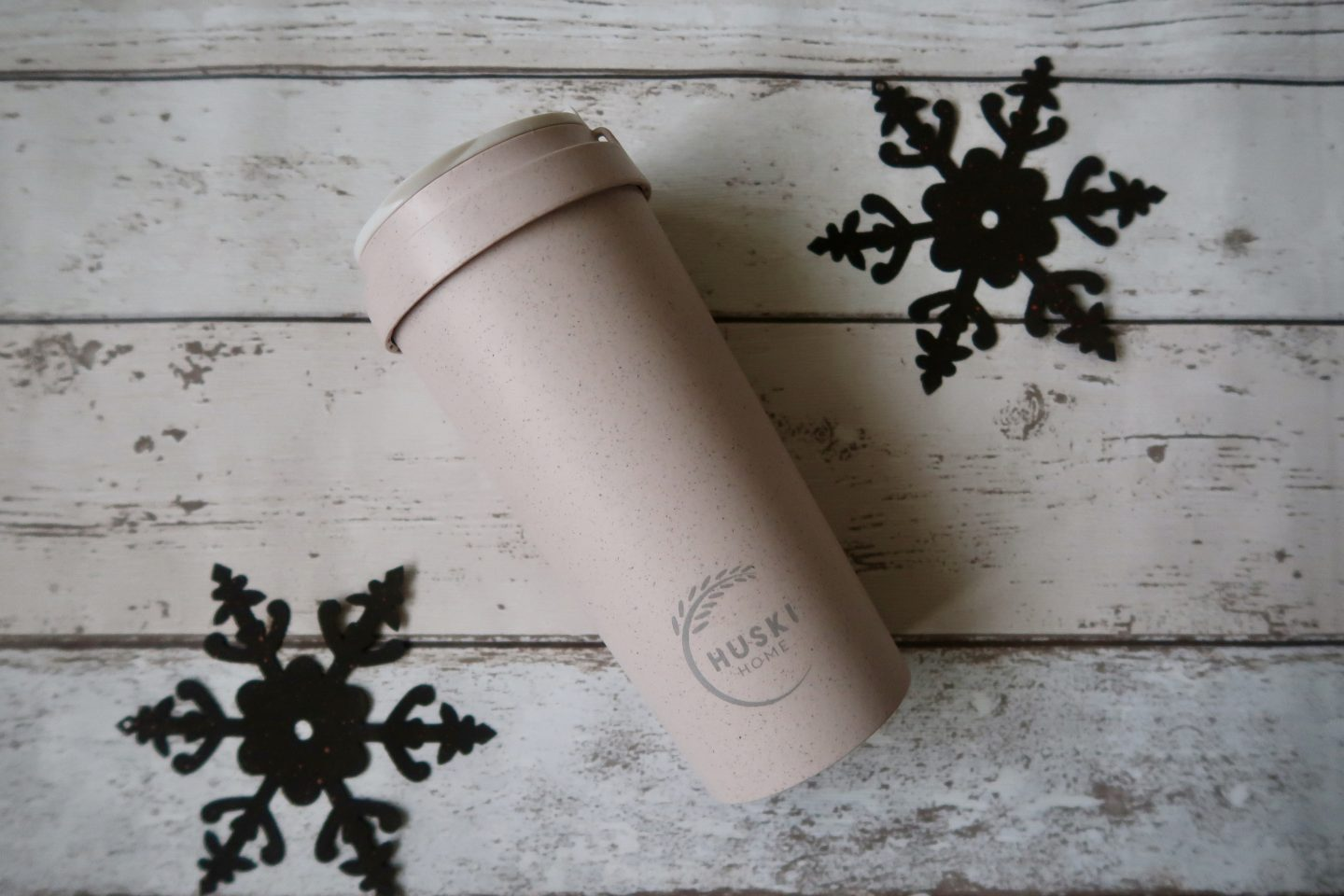 A pale pink travel cup lying on white wooden floorboards with 2 metal snowflakes