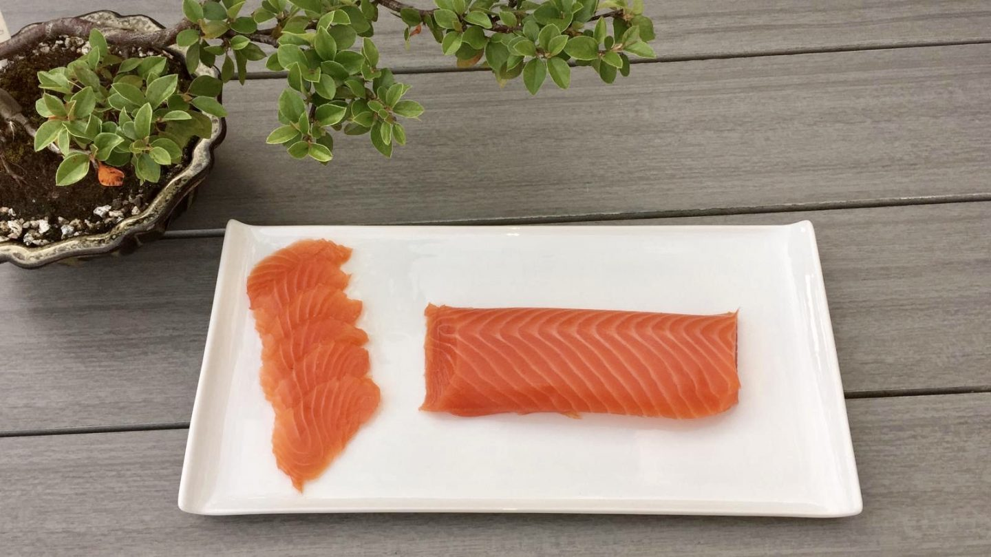 A rectangular white plate on a grey table, sat next to a bonsai plant. On the plate are some slices of Scottish smoked salmon fillet