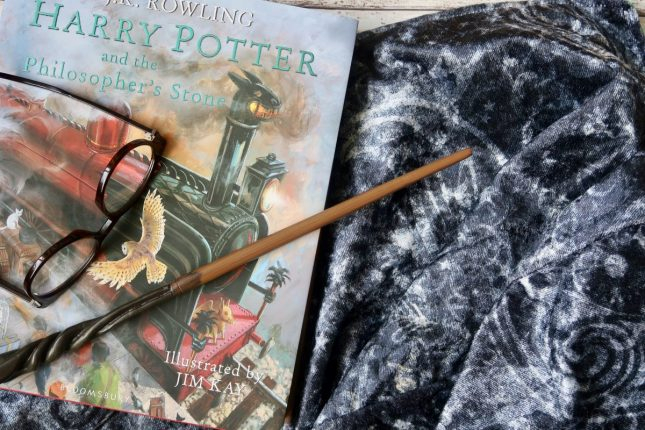 An illustrated copy of harry potter and the philosophers stone, round glasses and a magic wand lie on top of a grey patterned cloak