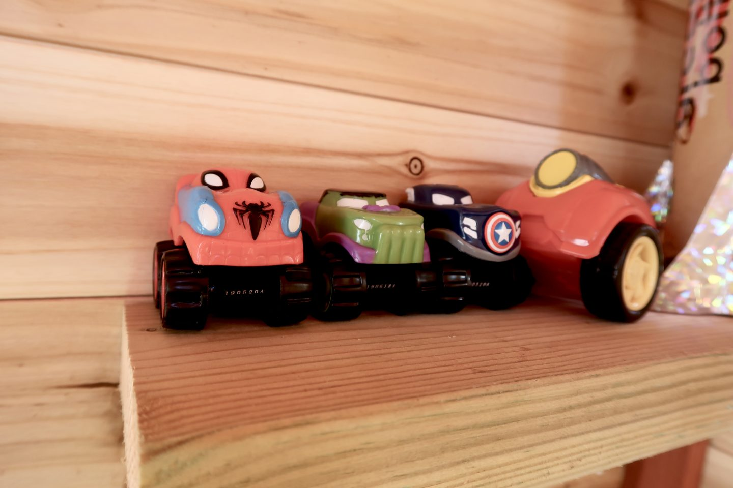 toy cars on a shelf, decorated in super hero designs