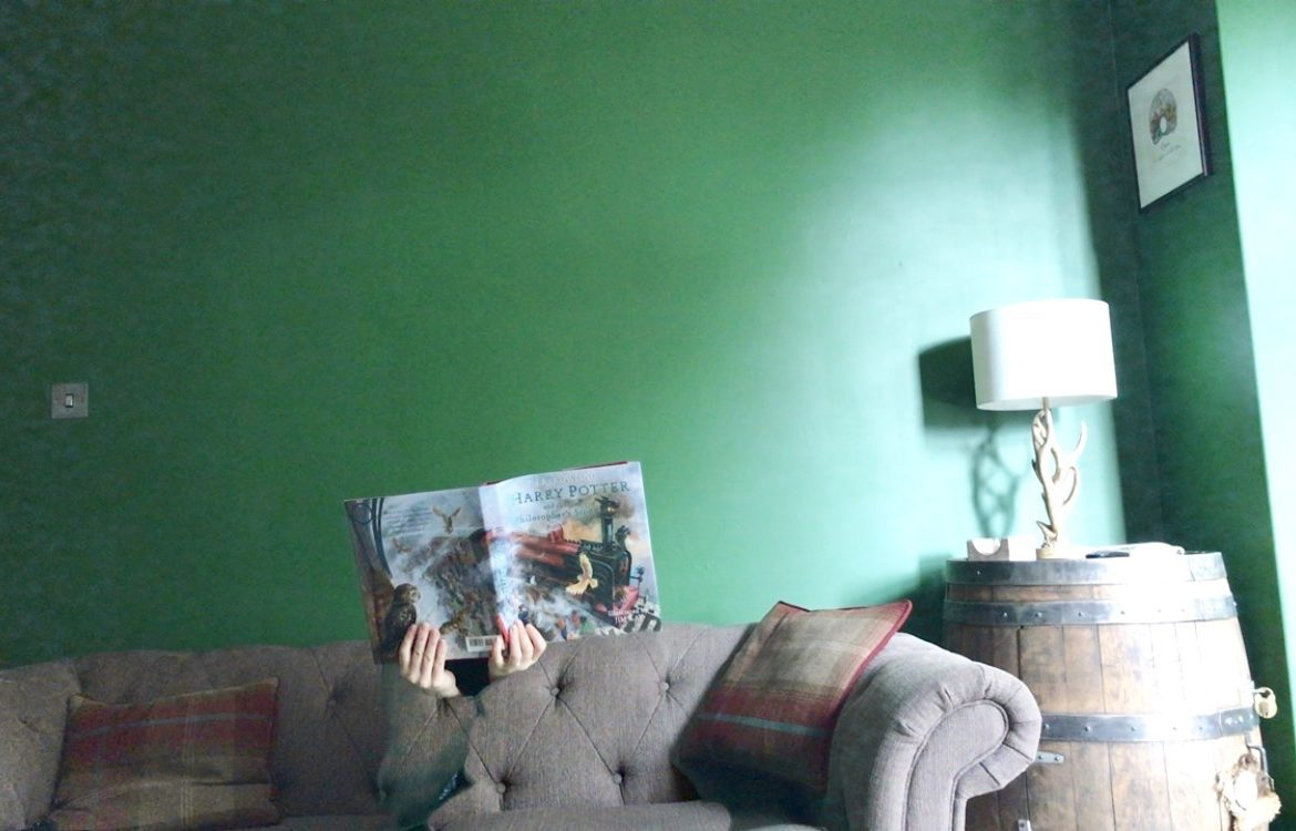 A green room with a sofa. two hands poke out of an invisibility cloak holding a Harry Potter book