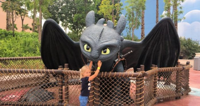 A child touching a black dragon, a character from How To Train Your Dragon