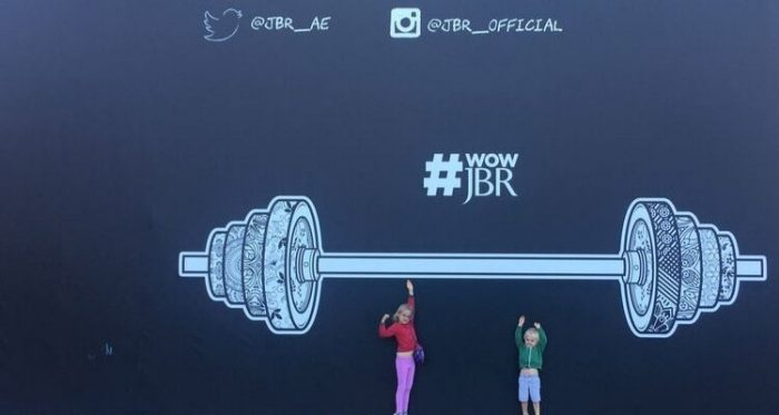 Street art on The Walk in Dubai. The image depicts 2 children pretending to lift a painting of some weights on a wall