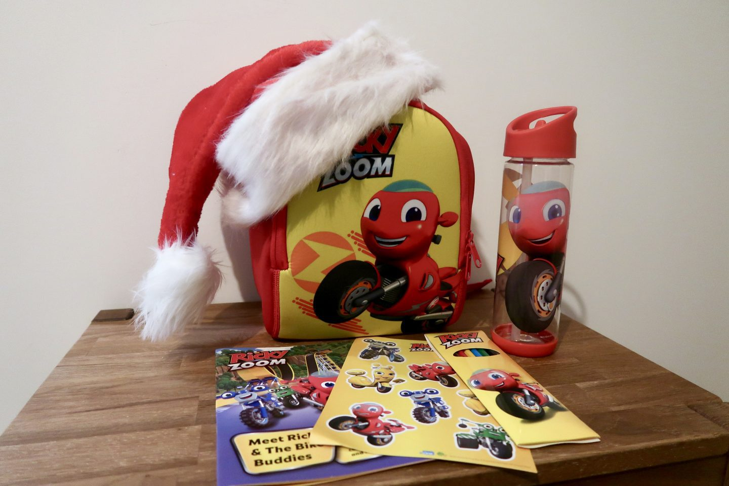 A child's backpack with the character Ricky Zoom, a red motorbike, on it and a Santa hat on the top. Next to it is a Ricky Zoom water bottle and in front are some stickers and activity books al with Ricky Zoom