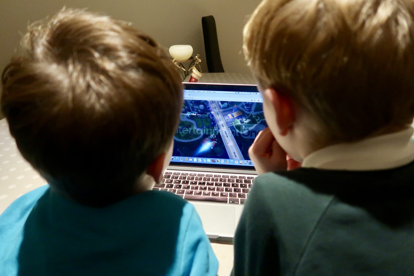 The backs of 2 boys heads as they watch a Ricky Zoom Christmas special episode on a Mac laptop