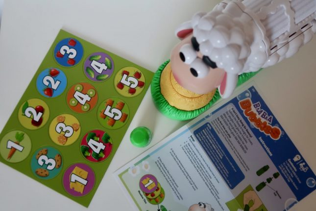 A green sheet with 12 circles with numbers on them, a plastic sheep and the instructions for a game called BaaBaa Bubbles