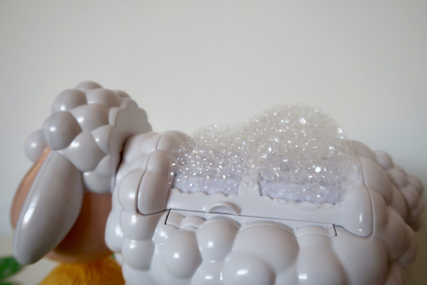 The back of a plastic sheep with bubbles all over it