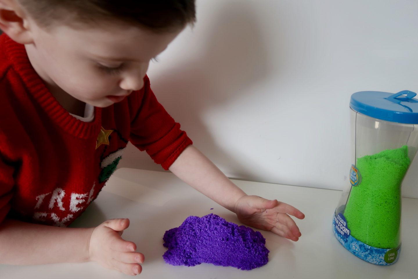 A boy in a red jumper playing with purple sensory sand on a white table. A tub with green sensory sand in it is next to him