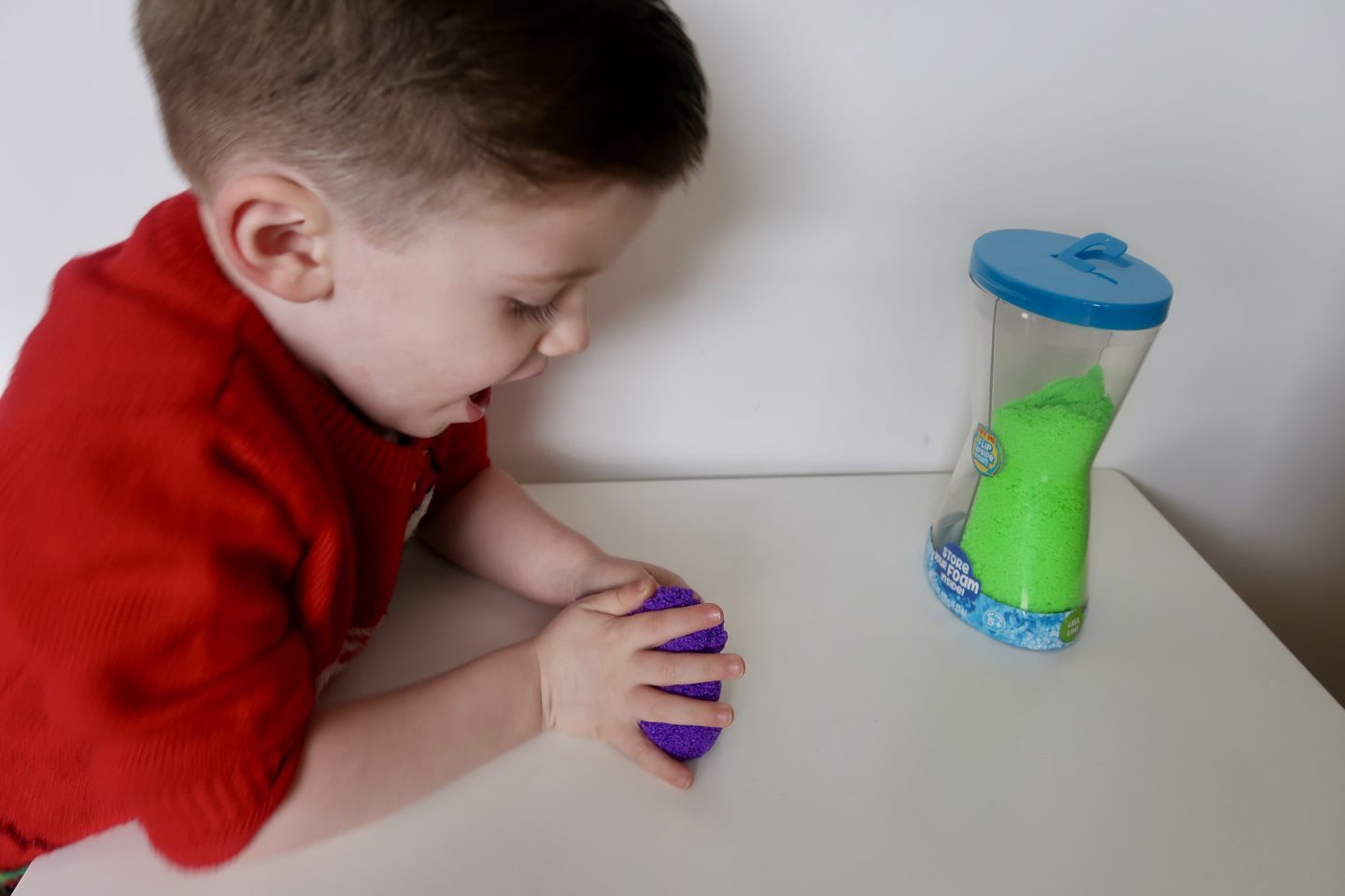 A boy in a red jumper playing with purple sensory foam