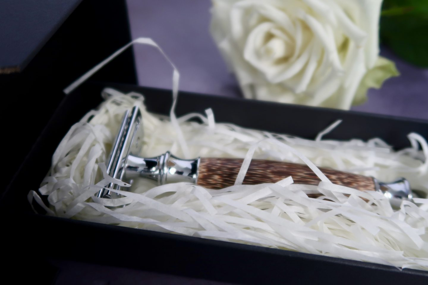 A wooden handled plastic free razor sitting in shredded paper within a box. A white rose is out of focus in the background