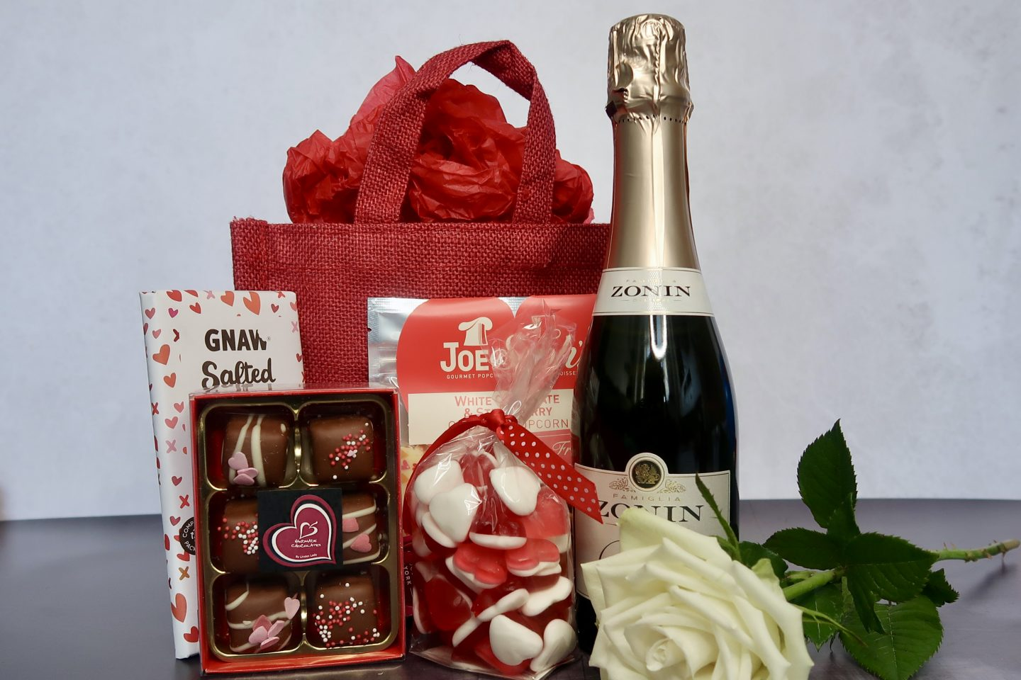 A Valentine's hamper full of treats, laid out in front of a red canvas bag