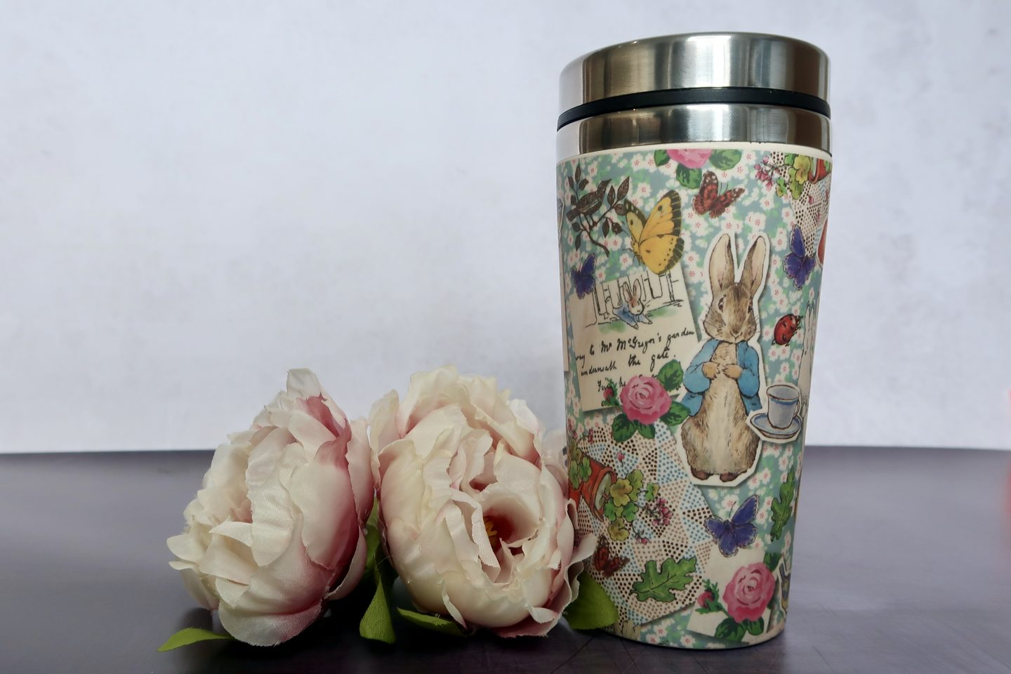 2 artifical flowers, next to a bamboo travel mug with a Peter Rabbit print on it