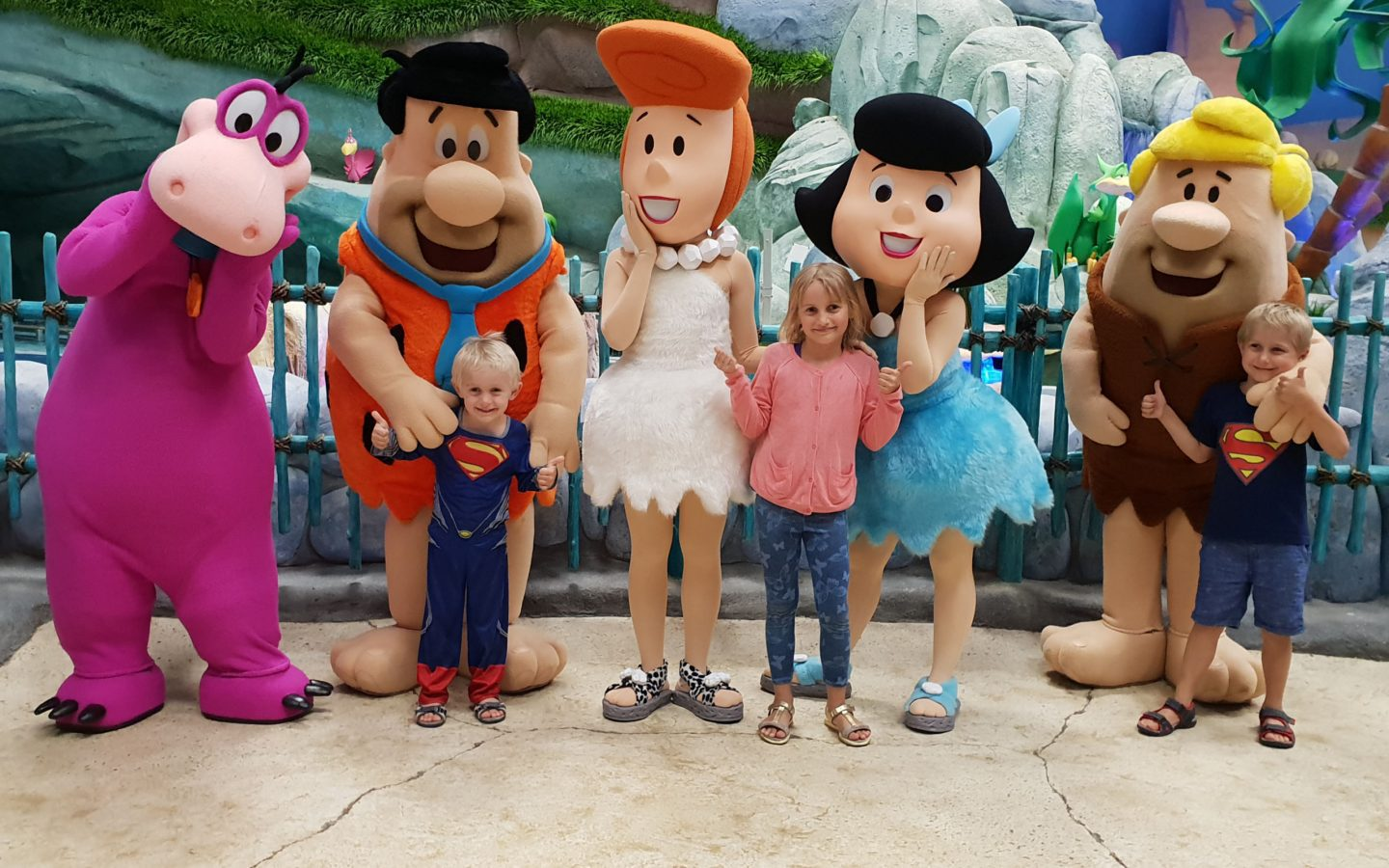 5 characters from the Flinstones pose with children