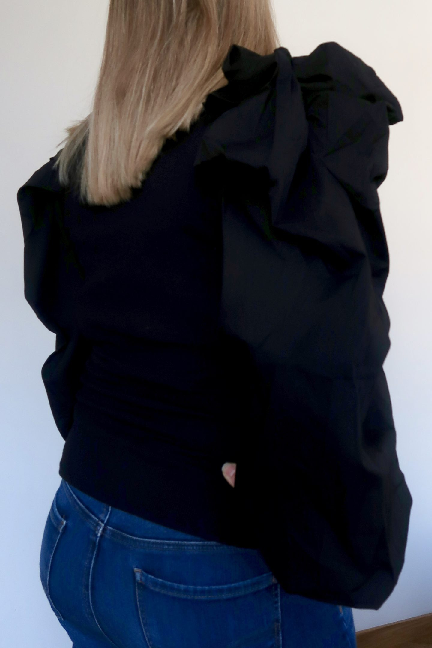 A woman facing away from the camera wearing a black puff sleeves top and blue jeans