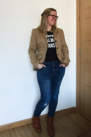 A woman in a black t-shirt and jeans with a brown blazer and chelsea boots