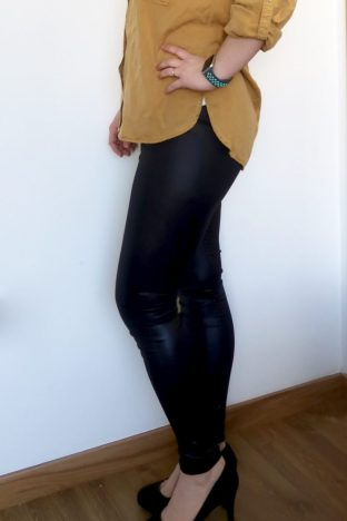 The legs of a woman wearing leather look trousers, a yellow shirt and black high heels