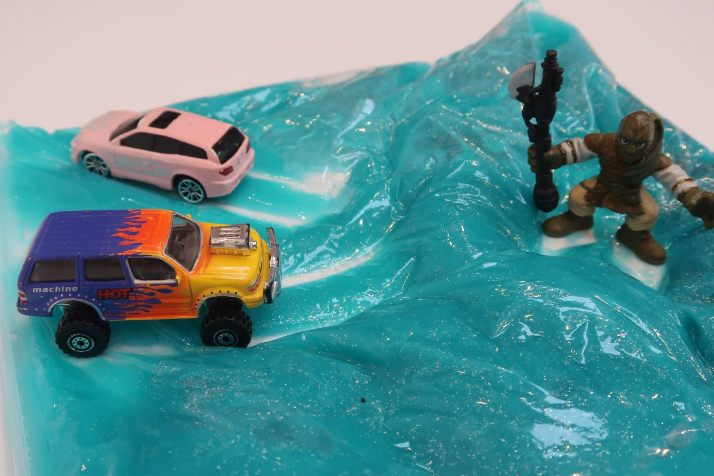 Blue slime in a plastic bag, with toy cars and a figure on top of it