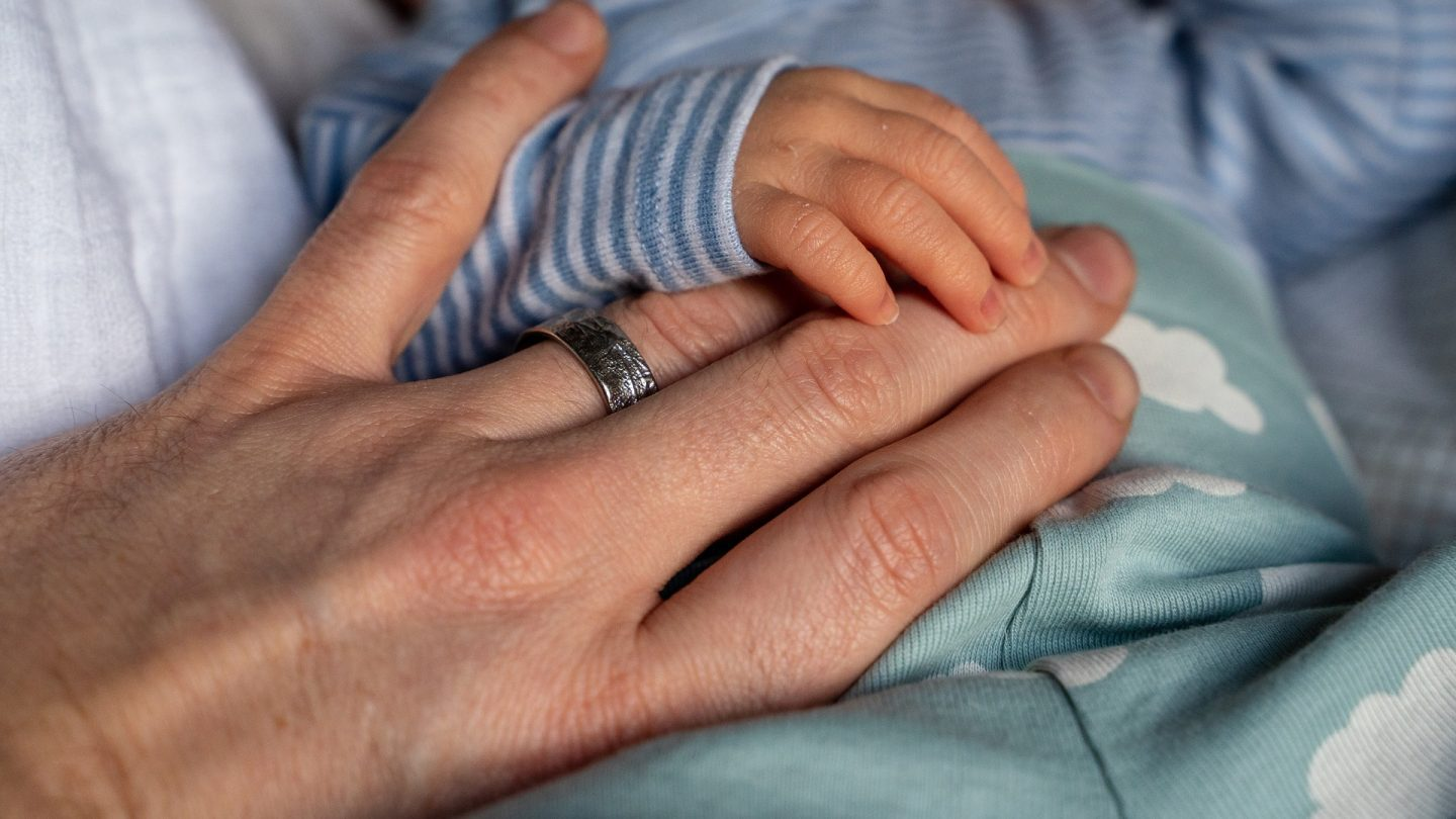A baby's hand lying on top of a mans hand