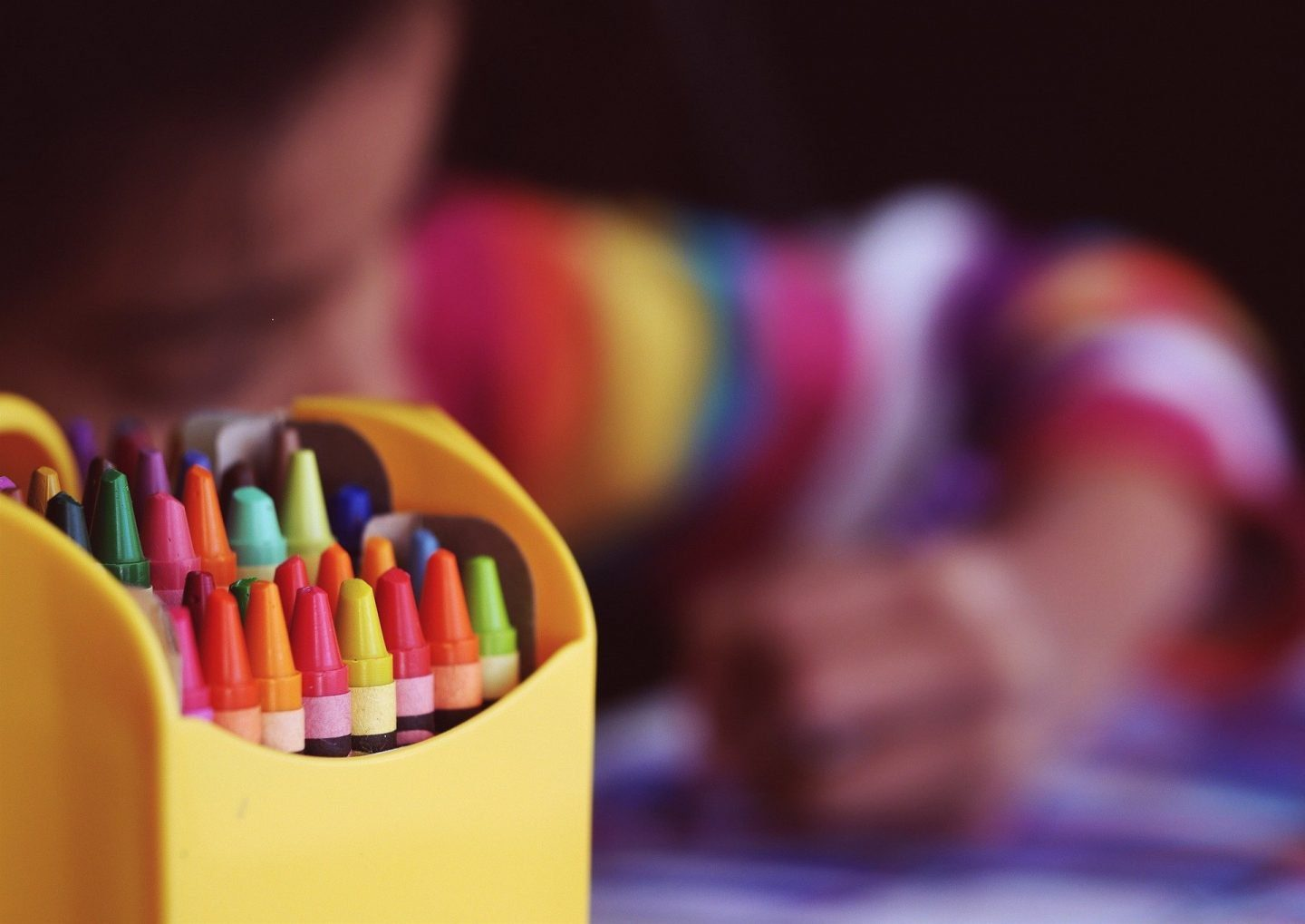 a box of crayons, with an out of focus child behind