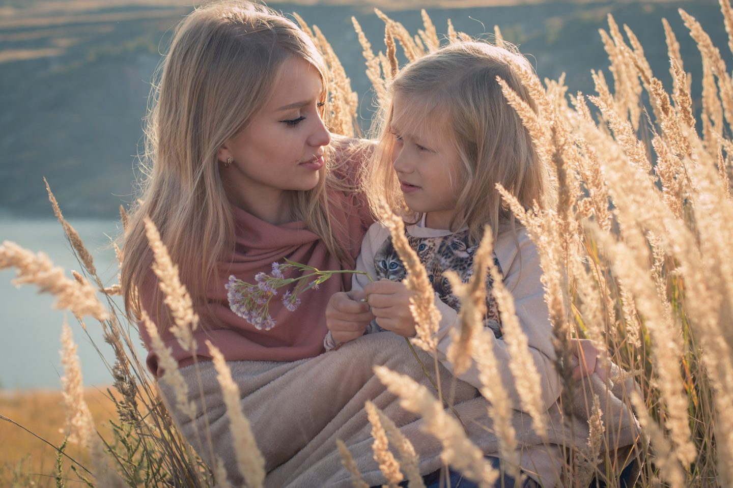 A mother and daughter sit amongst some wheat in golden light