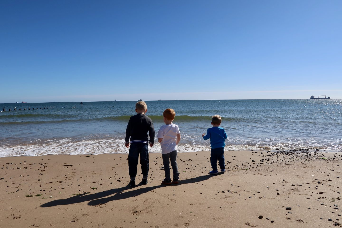 3 boys standing on the beach facing the sea