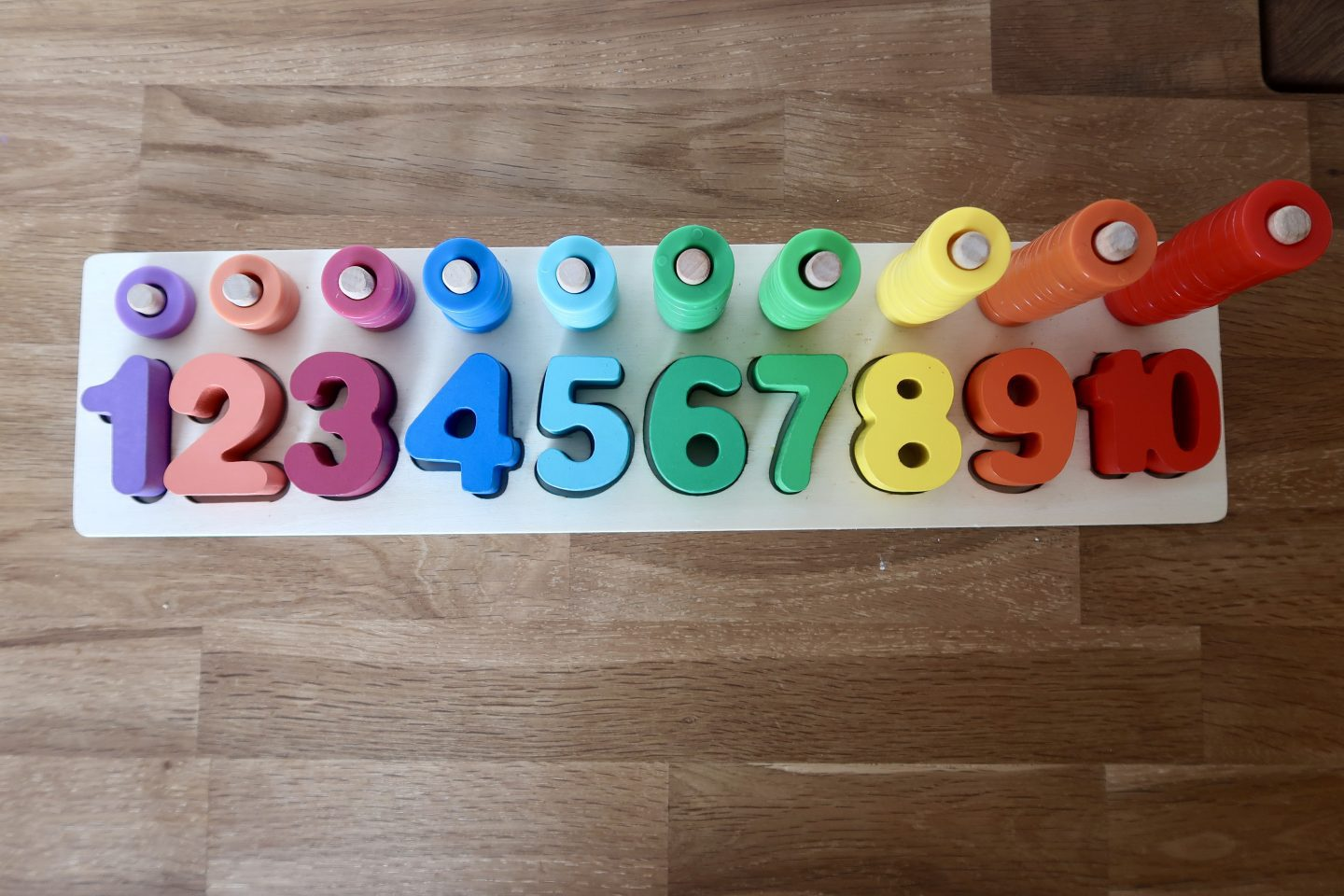 A rainbow coloured wooden counting toy. The numbers 1 to 10 are listed with corresponding coloured rings