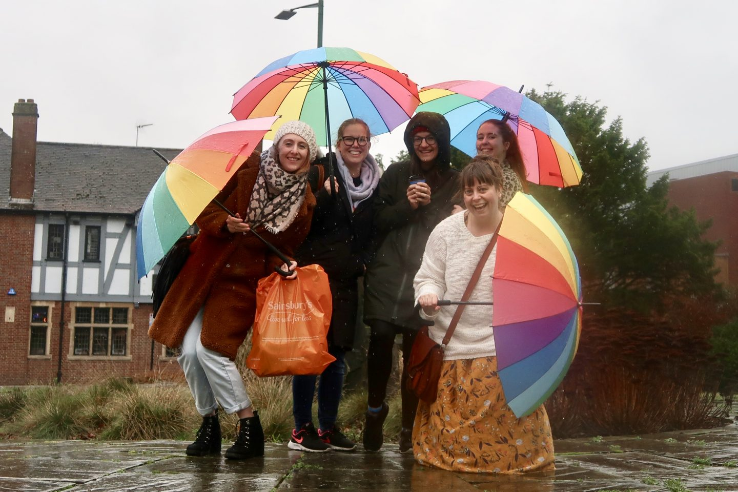 A group of women stand in the rain with rainbow umbrellas
