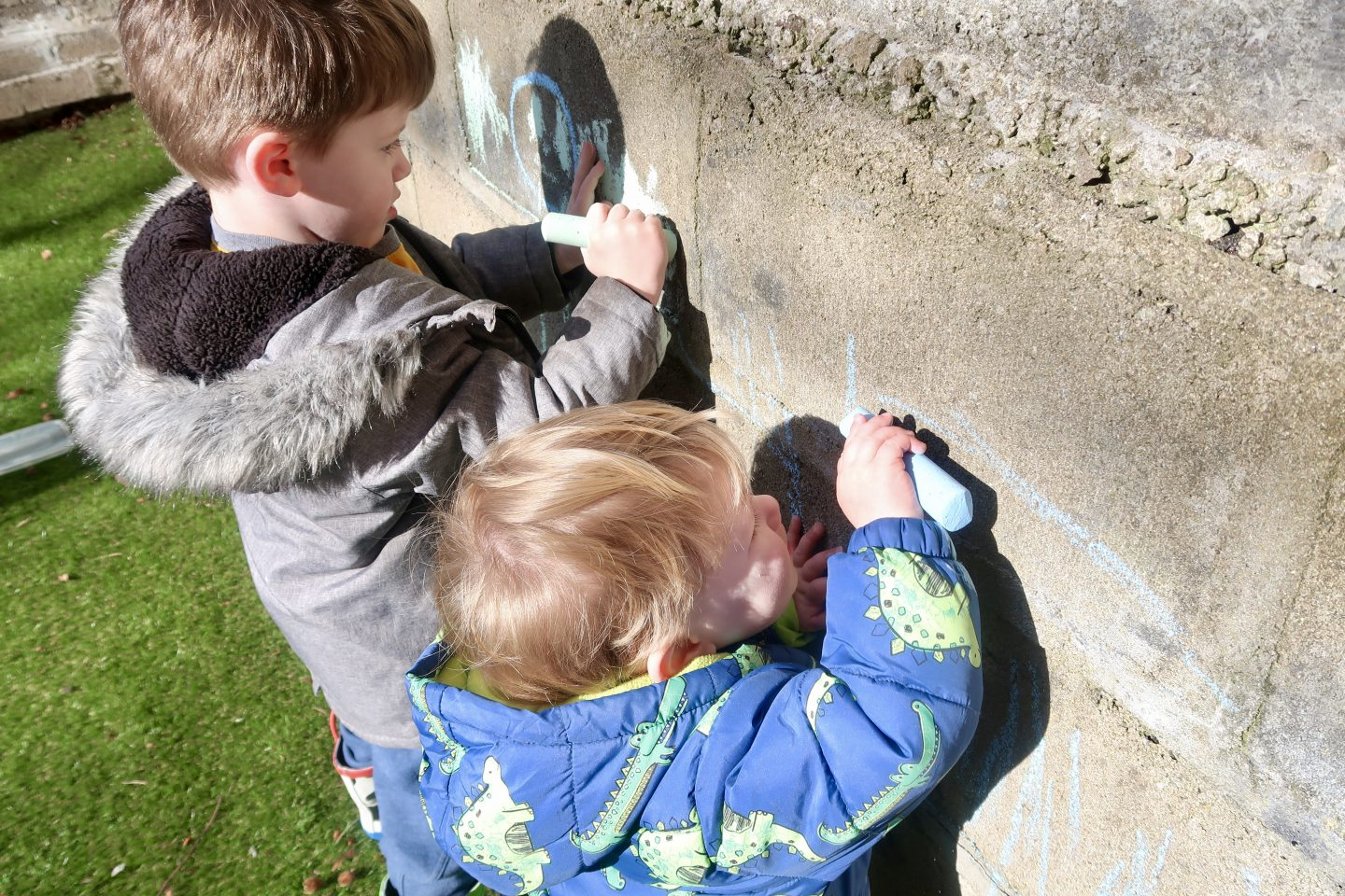 2 boys drawing on a brick wall will giant chalk