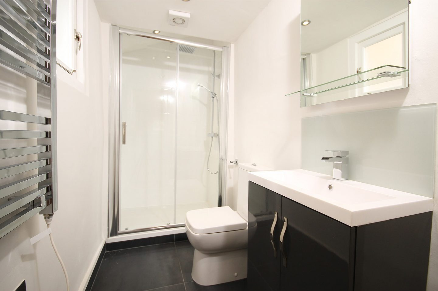 A bathroom with a shower that has glass doors. The floor is tiled in black