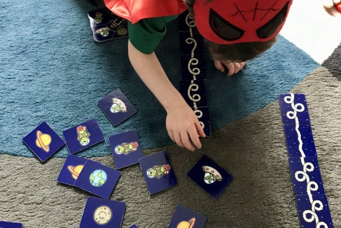 A child leaning over a card game with space themed images on the cards