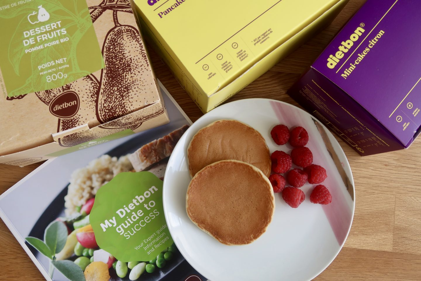 A plate of pancakes and raspberries surrounded by packaging for Dietbon meal delivery foods