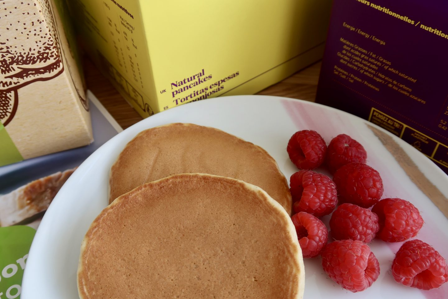 A white plate with 2 pancakes and some raspberries