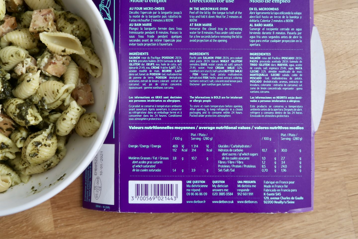 A close up on some food packaging showing the nutritional information, next to a bowl of pasta