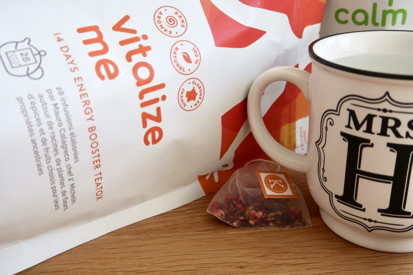 """A mug and tea bag next to a package that says """"vitalize me"""" on it"""