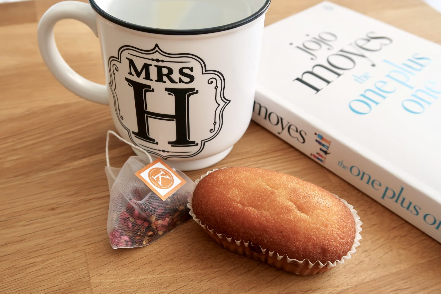 A mini loaf cake next to a mug and tea bag with a book in the background