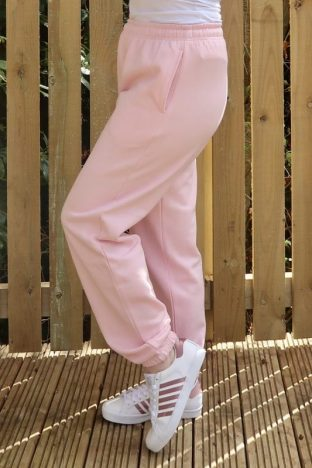 legs wearing pink joggers and white and pink trainers