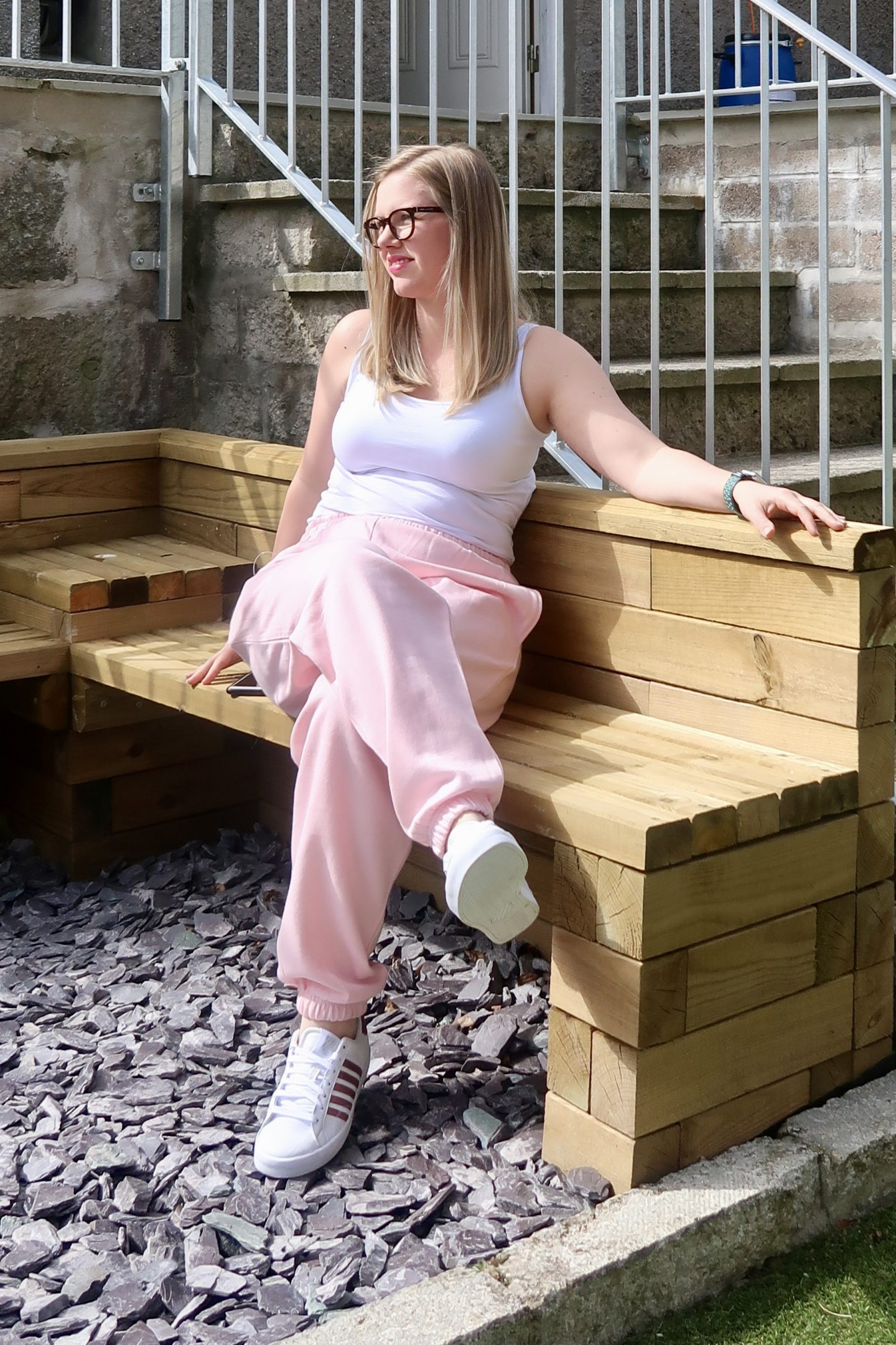 A girl sitting on a wooden bench wearing pink joggers and a white tank top
