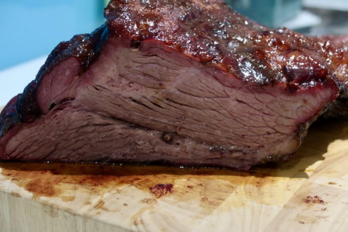 A smoked brisket on a large wooden chopping board