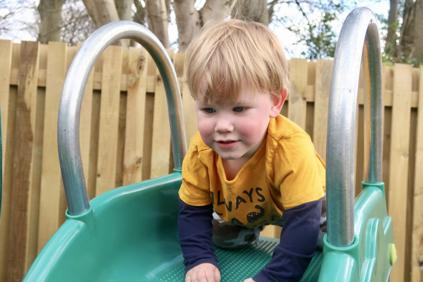 A boy at the top of a slide