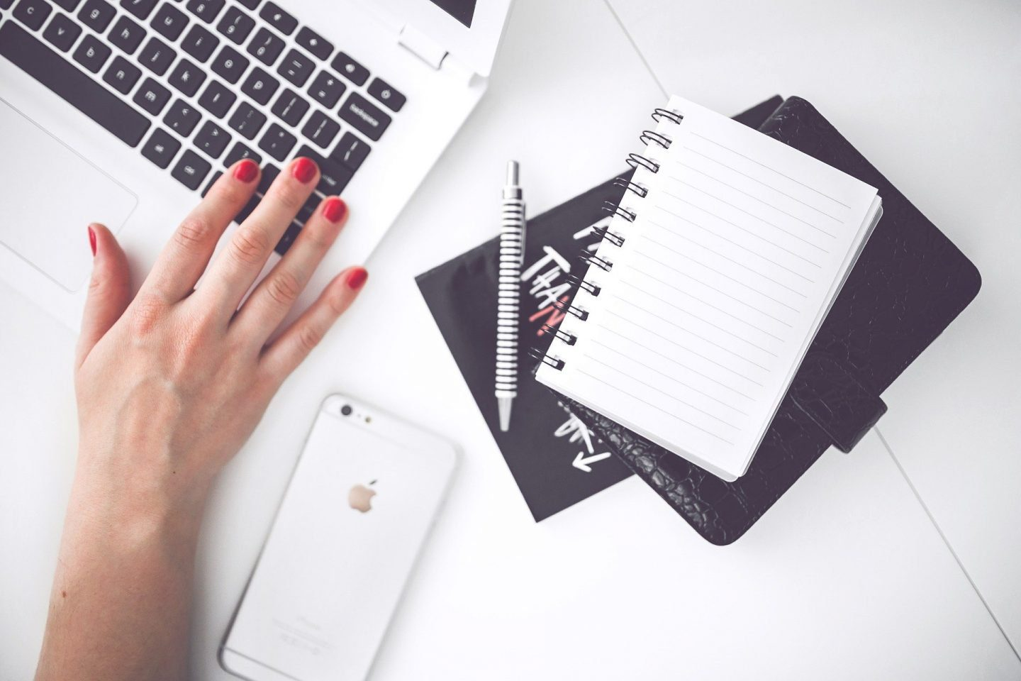 A hand on a laptop keyboard, an iphone and a notebook and pen on the desk next to it