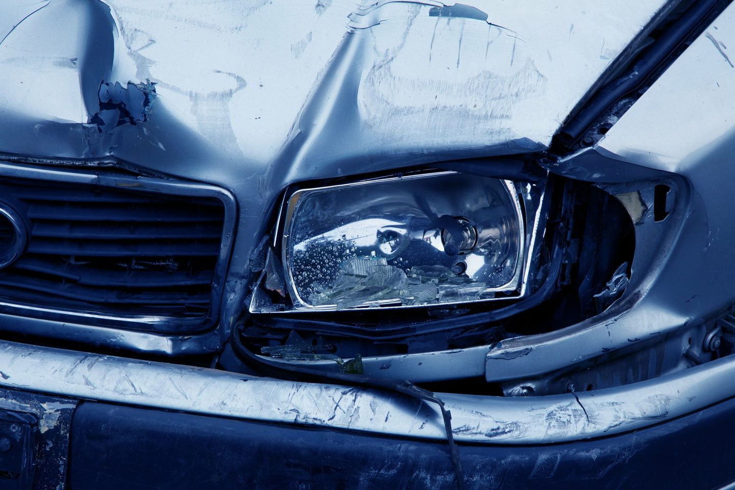 A grey car that has been in a crash. The image shows a close up of the headlamp and grill